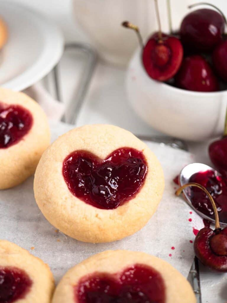 Heart shaped thumbprint cookies filled with fresh homemade cherry jam